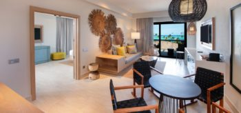 Sala de estar con mesa y terraza en resort Lopesan Costa Bávaro en Punta Cana